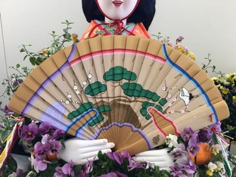 鴻巣びっくりひな祭り 鴻巣駅改札内 ひな人形花飾りです。おひなさまが持っている扇の木材がカナダツガです。白木の柾目に綺麗な絵を描いていただきました。